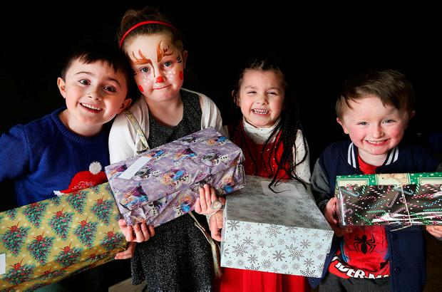 Colin Dunne (6), from East Wall, Courtney Kenny (6), from Clontarf, Colin's sister Layla Dunne (5), and Courtney's brother Matthew McGuinness (3) at the Christmas party in Coolock. Photo: Steve Humphreys