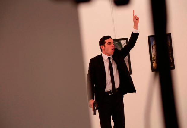 An unnamed gunman gestures after shooting the Russian Ambassador to Turkey, Andrei Karlov, at a photo gallery in Ankara, Turkey, Monday, Dec. 19, 2016. (AP Photo/Burhan Ozbilici)