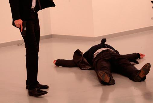 An unnamed gunman holds the gun after shooting the Russian Ambassador to Turkey, Andrei Karlov, at a photo gallery in Ankara, Turkey, Monday, Dec. 19, 2016. (AP Photo/Burhan Ozbilici)
