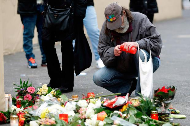 A man lights a candle in Berlin, Germany, Tuesday, Dec. 20, 2016, the day after a truck ran into a crowded Christmas market and killed several people. (AP Photo/Matthias Schrader)