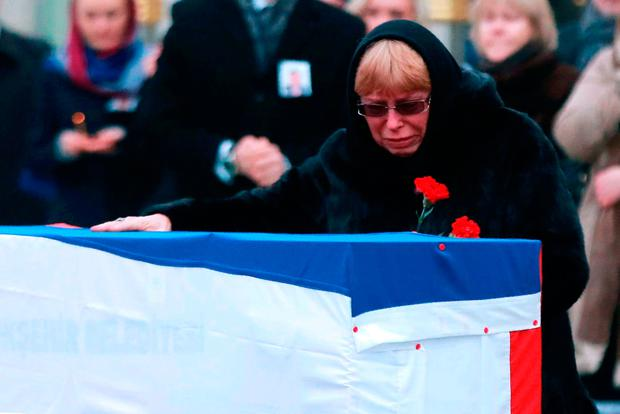 Marina Karlova, widow of late Russian Ambassador to Turkey Andrei Karlov, in front of his coffin at Ankara's Esenboga Airport. Photo: AFP/Getty Images
