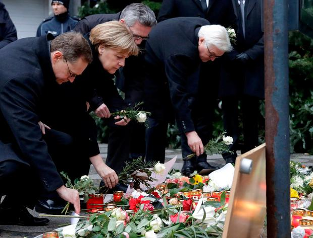 The Mayor of Berlin Michael Mueller, German Chancellor Angela Merkel, German Interior Minister Thomas de Maiziere and German Foreign Minister Frank-Walter Steinmeier lay flowers at the Christmas market in Berlin, Germany, yesterday. Photo: AP