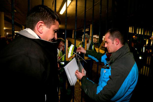 Agents acting for Apollo House attach a court notice to vacate the building to the gates. Photo: Gerry Mooney