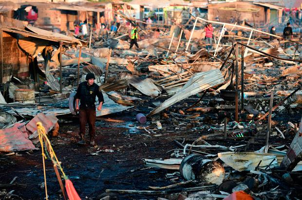 Firefighters work amid the debris left by a huge blast that occurred in a fireworks market in Mexico City, on December 20. Photo: AFP/Getty Images