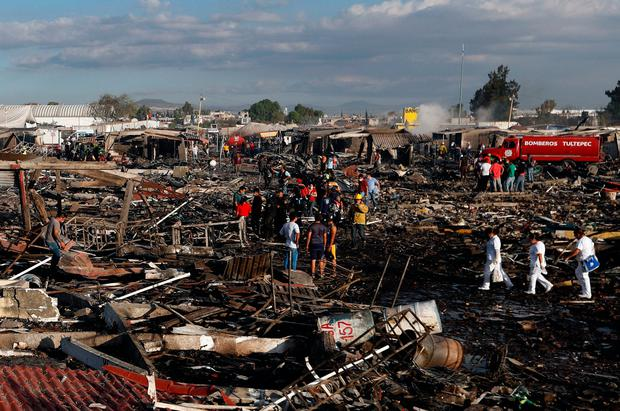 Firefighters and rescue workers walk through the scorched ground of Mexico's best-known fireworks market after an explosion explosion ripped through it, inTultepec, Mexico. Photo: AP