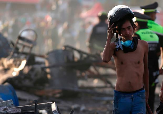 A boy takes his helmet off as he pauses while working at the scorched ground of the open-air San Pablito fireworks market, in Tultepec, outskirts of Mexico City, Mexico, Tuesday, Dec. 20, 2016. (AP Photo/Eduardo Verdugo)