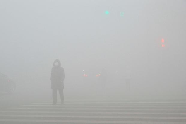 People walk past a street in heavy smog during a polluted day in Weifang, Shandong province, December 20, 2016. Picture taken December 20, 2016. REUTERS/Stringer