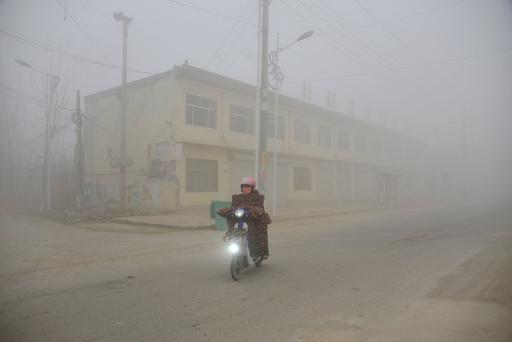 A cyclist rides along a street in heavy smog during a polluted day in Liaocheng, Shandong province, December 20, 2016.