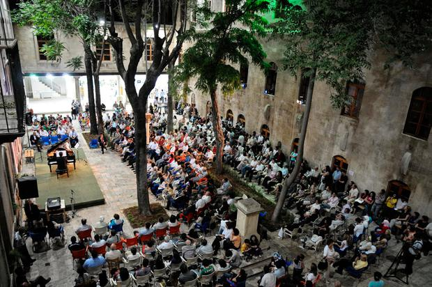 People attend a music concert in al-Sheebani school's courtyard, in the Old City of Aleppo, Syria June 6, 2009. REUTERS/Omar Sanadiki