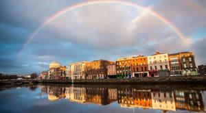 A full rainbow over the Four Courts and quays along the River Liffey in Dublin City, Ireland.