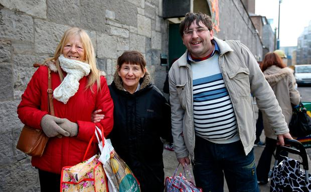 Angela Foy, Marie McCabe and Michael McCabe after they collected their food parcels. Photo: Gerry Mooney