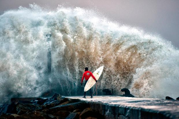 A huge wave crashes against Castlerock pier as professional surfer Al Mennie waits on a break in the swell in Coleraine, Northern Ireland. Photo by Charles McQuillan/Getty Images
