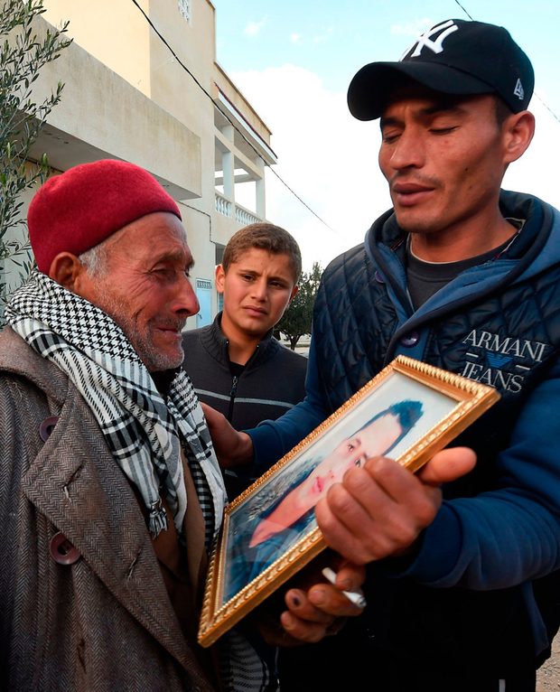 Walid Amri (right) and Mustapha Amri, the father and brother of 24-year-old Anis Amri, mourn with a portrait of Anis in front of the family house in the town of Oueslatia, in Tunisia's Kairouan region, yesterday. Photo: Getty
