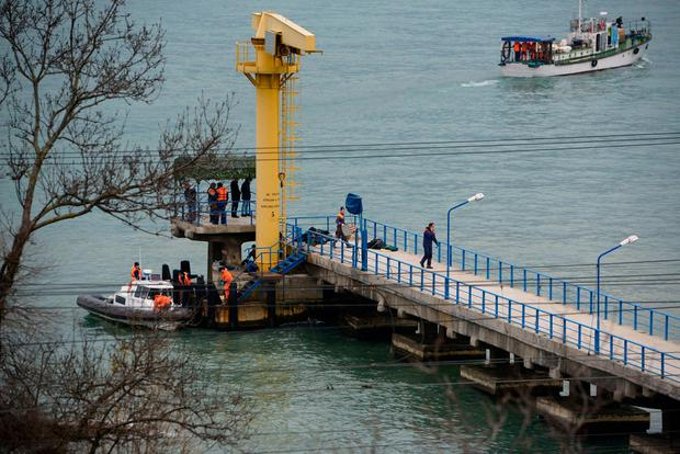 Russian rescue workers collect wreckage of the crashed plane at a pier just outside Sochi, Russia, Sunday, Dec. 25, 2016 (AP Photo/Viktor Klyushin)