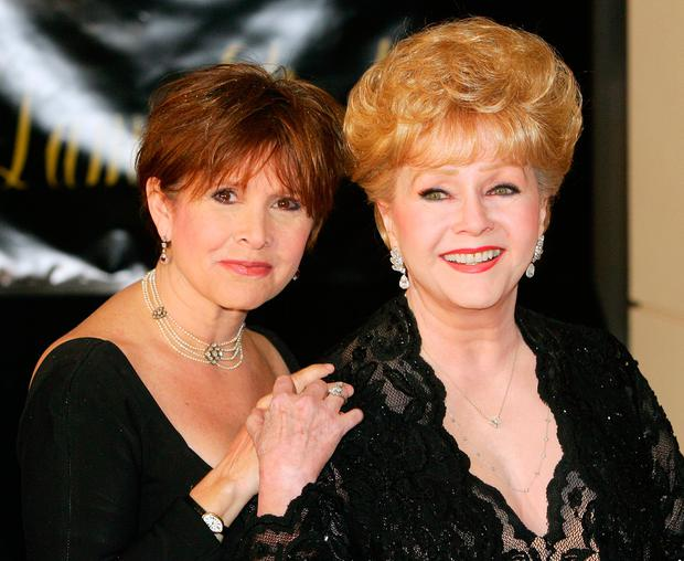 Actress Carrie Fisher (L) and her mother, actress Debbie Reynolds, arrive for Dame Elizabeth Taylor's 75th birthday party at the Ritz-Carlton, Lake Las Vegas on February 27, 2007 in Henderson, Nevada. (Photo by Ethan Miller/Getty Images)