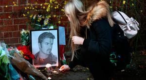 A woman lays a candle outside the Goring house of George Michael in Oxfordshire. Photo: Andrew Matthews/PA Wire
