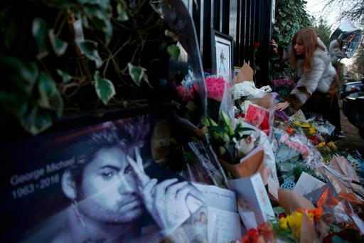 A woman lays flowers outside the house of singer George Michael, in north London, Britain December 26, 2016. REUTERS/Neil Hall