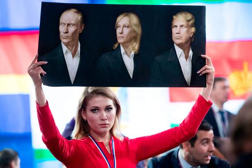 A journalist holds a poster with portraits of Russian President Vladimir Putin, France's far-right National Front president Marine Le Pen and US president-elect Donald Trump during a protest in Moscow last week. Photo: AP