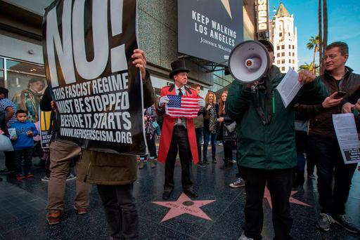 Trump supporter Gregg Donovan holds a flag over the Hollywood Walk of Fame star for Donald Trump as people protest against the US president-elect on Christmas Day in Los Angeles, California. Photo: David McNew/Getty