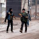 Youths carry weapons along a road in al-Rai town, north of Aleppo in Syria. Photo: Reuters/Khalil Ashawi