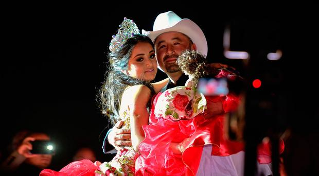 Rubi Ibarra and her father Cresencio Ibarra dance during the celebration of her 15th birthday in Villa Guadalupe, San Luis Potosi State, on December 26, 2016. / AFP PHOTO / RONALDO SCHEMIDTRONALDO SCHEMIDT/AFP/Getty Images