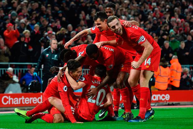 Liverpool's Brazilian midfielder Roberto Firmino is mobbed by his team-mates after scoring his side's second goal against Stoke City in their 4-1 victory at Anfield last night. Photo: AFP/Getty