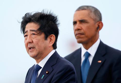 Japanese Prime Minister Shinzo Abe, left, joined by President Barack Obama, speaks on Kilo Pier overlooking the USS Arizona Memorial, part of the World War II Valor in the Pacific National Monument, in Joint Base Pearl Harbor-Hickam, Hawaii, Tuesday, Dec. 27, 2016. (AP Photo/Carolyn Kaster)