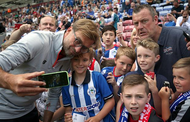 WIGAN, ENGLAND - JULY 17: Jurgen Klopp manager of Liverpool takes a selfie with fans during the Pre-Season Friendly match between Wigan Athletic and Liverpool at JJB Stadium on July 17, 2016 in Wigan, England. (Photo by Nigel Roddis/Getty Images)