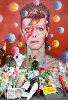 Farewell: Floral tributes left beneath a mural for David Bowie