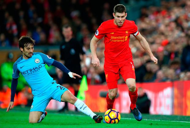 David Silva of Manchester City and James Milner of Liverpool clash. Photo by Clive Brunskill/Getty Images