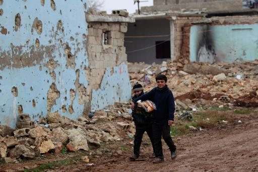 Boys carry bread near damaged buildings in al-Rai town, north of Aleppo. Photo: Reuters/Khalil Ashawi