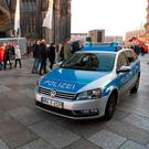 A police car drives past the Cologne Cathedral near the station square. Photo: Getty Images