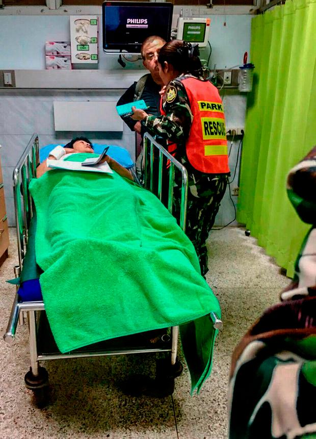 French national Muriel Benetulier (L) lies on a stretcher as she speaks with a Thai park ranger (R) at a local medical facility after she was bitten by a crocodile. Photo: HO/AFP/Getty Images