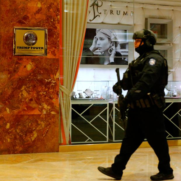 A New York City Police officer assigned to protect U.S. President-elect Donald Trump walks past a picture of Trump's daughter Ivanka Trump in the lobby of Trump Tower in New York, U.S. January 2, 2017. REUTERS/Jonathan Ernst