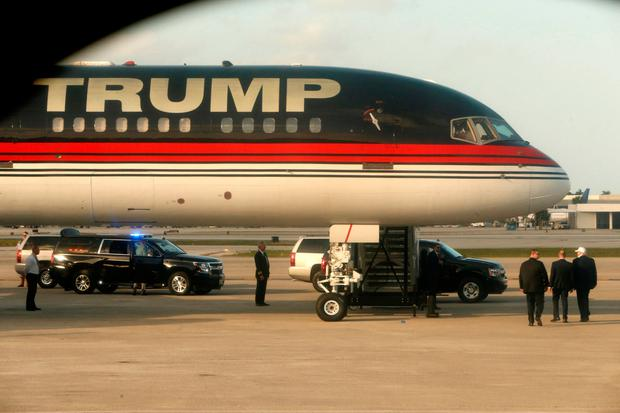 U.S. President-elect Donald Trump (bottom R, wearing cap) boards his plane at Palm Beach International Airport to depart for travel to New York after spending the holidays at the Mar-a-lago Club, in West Palm Beach, Florida, U.S. January 1, 2017. REUTERS/Jonathan Ernst