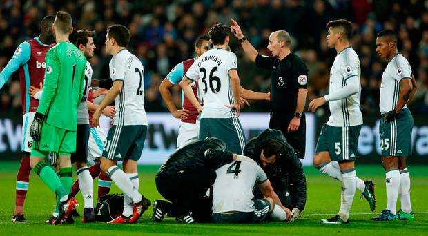 Referee Mike Dean gestures after sending off West Ham United's Sofiane Feghouli