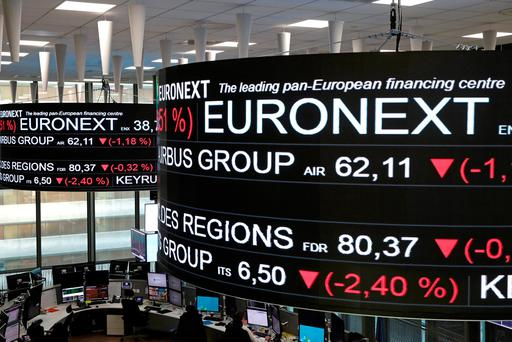 Stock price information is displayed on screens as they hang above the Paris stock exchange