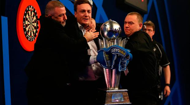 A spectators invades the oche and lift up the Sid Waddell trophy