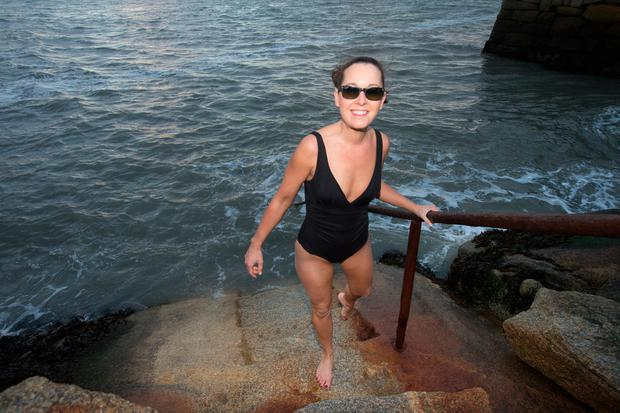 Maria Fitzgerald from Foxrock emerges after taking the plunge into the cold stormy waters at Sandycove beach on New Year's Day. Photo: Tony Gavin
