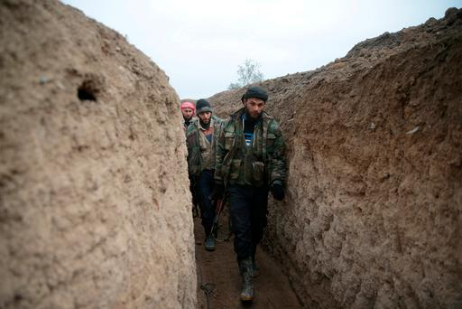 Rebel fighters walk inside a trench on the forth day of the truce, on al-Rayhan village front near the rebel held besieged city of Douma, in the eastern Damascus suburb of Ghouta. Photo: Reuters