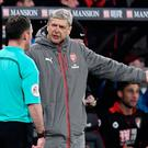 Arsenal manager Arsene Wenger remonstrates with assistant referee during last night's game