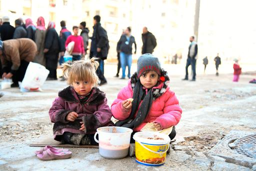 Girls eat a cooked meal provided by the UN through a partner NGO in the eastern Aleppo neighbourhood of Tariq al-Bab, Syria. Photo: UNHCR/Reuters