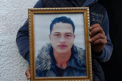 A family member holds a portrait of 24-year-old Anis Amri, the prime suspect in Berlin's deadly truck attack