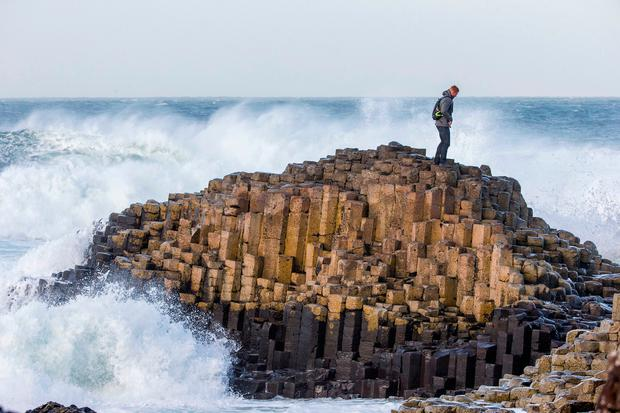An American tourist climbs down from The Honeycomb at the Giant's Causeway on December 23. Photo: Liam McBurney/PA Wire