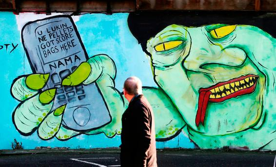 A member of the public looks at a mural referencing the RHI crisis and Northern Ireland First Minister Arlene Foster in a Belfast city centre car park. Photo: Niall Carson/PA Wire