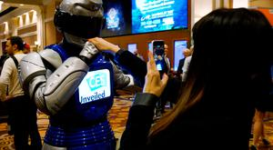 A man in a mechanized robotic costume kisses a woman's hand as she takes a picture of the encounter at the CES Unveiled event at CES in Las Vegas, January 3, 2017. REUTERS/Rick Wilking