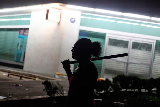 A woman holds a stick as she and other neighbors try to prevent looting in the port city of Veracruz, Mexico, Thursday Jan. 5, 2017. Anger over gasoline prices hikes in Mexico fueled more protests and looting Thursday, and officials said the unrest had resulted in the deaths of several people and the arrests of hundreds.(AP Photo/Felix Marquez)