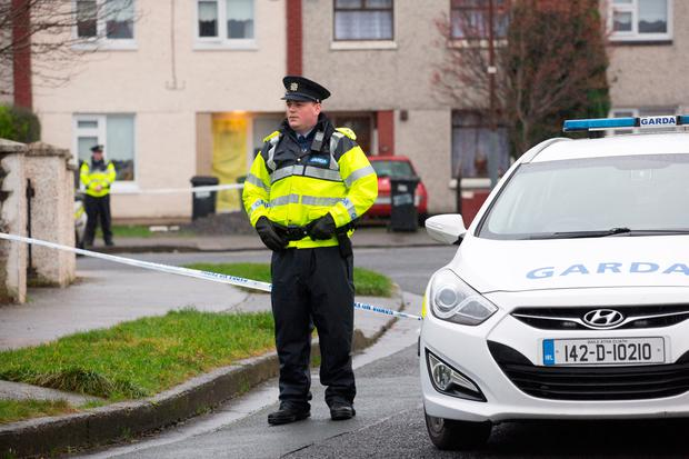 Gardai on duty outside the house in Kilclare Crescent, Jobstown where 17 year old Reece Cullen was stabbed to death. Photo: Tony Gavin