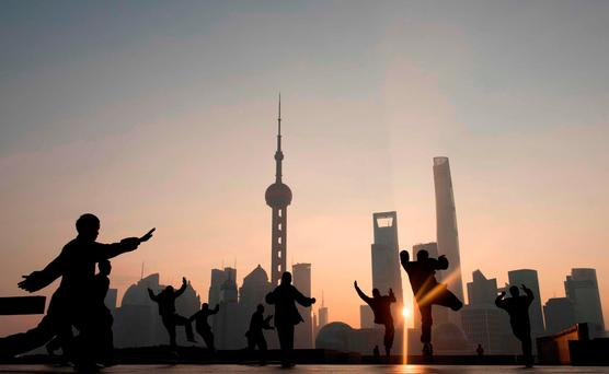 People perform morning exercises against the backdrop of Shanghai's financial district. Chinese investment in Donald Trump's America is likely to cause US assest prices to soar. Photo: Getty