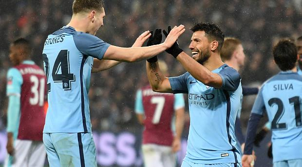 Manchester City's Argentinian striker Sergio Aguero (3rd R) celebrates with Manchester City's English defender John Stones after scoring their fourth goal during the English FA cup third round football match between West Ham United and Manchester City at the London Stadium in east London on January 6, 2016
